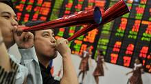 Traders blow horns during the year-end closing of trade in front of a giant electronic board at the Philippine Stock Exchange in Manila on December 29, 2011. (NOEL CELIS/NOEL CELIS/AFP/Getty Images)