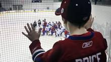Seven year old Sam Beland watches the Montreal Canadiens NHL hockey team as they begin their official training camp in Brossard, Quebec January 13, 2013. (CHRISTINNE MUSCHI/REUTERS)