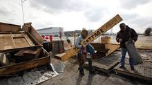 Electro-Motive Canada employees clean up the picket line after accepting a severance package: Caterpillar slammed the doors on the plant in February and shunted production to the U.S. (Deborah Baic/The Globe and Mail/Deborah Baic/The Globe and Mail)