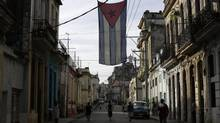 A Cuban flag hangs from a building in Havana December 27, 2014. Cuba's most prominent dissidents say they have been kept in the dark by U.S. officials over a list of 53 political prisoners who will be released from jail as part of a deal to end decades of hostility between the United States and Cuba. (ENRIQUE DE LA OSA/REUTERS)