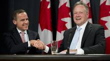 Bank of Canada Governor designate Stephen Poloz (right) shakes hands with outgoing Governor Mark Carney during a news conference in Ottawa, on Thursday May 2, 2013. (Adrian Wyld/THE CANADIAN PRESS)