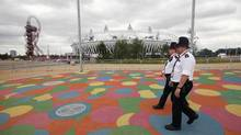 Police officers walk past the Olympic Stadium, in the Olympic Park, in Stratford, east London, July 17, 2012. The head of G4S admitted his management of the London Olympics staffing scandal had embarrassed the British government and left the world's biggest security firm's reputation in tatters as he fought to save his job on Tuesday. G4S has been at the centre of a political firestorm, and has lost about 650 million pounds ($1 billion) in market value, since it announced it could not provide the promised 10,400 Olympic security guards just two weeks before the Games. (ANDREW WINNING/REUTERS)