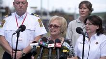 Lac-Megantic mayor Colette Roy-Laroche, flanked by security officials, speaks at a news conference in Lac-Megantic, Que., July 13, 2013. (Jacques Boissinot/THE CANADIAN PRESS)