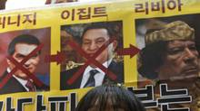A South Korean college student stands under photos of Tunisian President Zine al-Abidine Ben Ali, left, Egyptian President Hosni Mubarak and Libyan leader Moammar Gadhafi, right, during a rally to support the democracy movement in Libya, in front of the Libyan embassy in Seoul, South Korea, Wednesday, Feb. 23, 2011. (Ahn Young-joon/AP/Ahn Young-joon/AP)