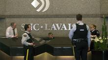 Royal Canadian Mounted Police (RCMP) officers stand in the headquarters of SNC Lavalin in Montreal April 13, 2012. Canada's Mounties were searching the Montreal headquarters of engineering giant SNC-Lavalin Group Inc on Friday following an internal company investigation that found a mysterious $56 million in improperly authorized payments. (CHRISTINNE MUSCHI/REUTERS)