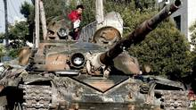 In this Tuesday, July 24, 2012 photo, a Syrian boy sits atop a damaged military tank at the border town of Azaz, some 20 miles (32 kilometers) north of Aleppo, Syria. (Turkpix/Associated Press)
