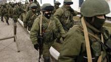Unidentified armed men patrol around a Ukraine's infantry base in Perevalne, Ukraine, on March 2, 2014. (Darko Vojinovic/AP)