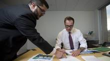 Louis Bergeron (R) , vice president, Quebec & New Brunswick, Energy East Pipeline, TransCanada sifts through paperwork his offices with staff member Jonathan Abecassis (Communications) in downtown Montreal, February 1, 2016. (Christinne Muschi For the Globe and Mail)