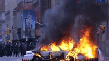 A police car burns after anti G20 summit protesters set fire to it in downtown Toronto. (Frank Gunn/Frank Gunn/The Canadian Press)