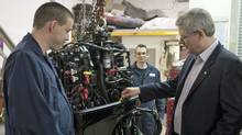 Conservative Leader Stephen Harper checks the oil on a marine engine as a mechanic looks on during a campaign stop in Regina on March 29, 2011. (Adrian Wyld/THE CANADIAN PRESS)