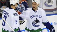 Vancouver Canucks defenseman Willie Mitchell comes over to celebrate a goal by Kyle Wellwood during a preseason hockey game in Edmonton, Alberta on Sunday, September 27, 2009. (Jimmy Jeong)