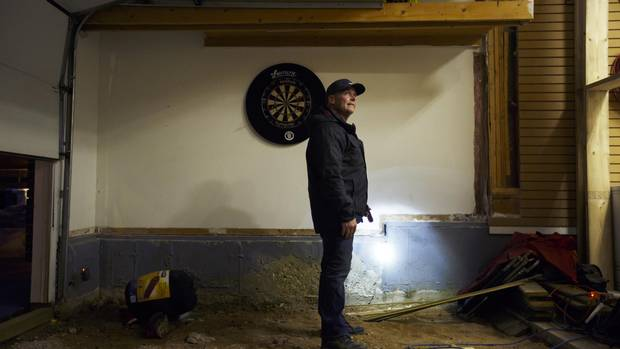 Kirby Byrne surveys damage to his Fort McMurray home last month. The house survived the fire but damage from water-bombing planes made it uninhabitable.