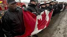 Sailors wait on an overpass for the motorcade carrying Lieutenant Andrew F. Webster as it heads to Halifax from the airport on Jan. 6, 2014. Webster, an officer on HMCS Toronto, was found dead while on shore leave in the Seychelles. (ANDREW VAUGHAN/THE CANADIAN PRESS)