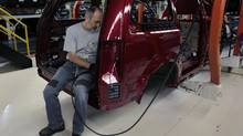 A Chrysler auto assembly worker is seen in this file photo. Statscan says factory sales rose 1.1 per cent in April. (© Rebecca Cook / Reuters/Reuters)