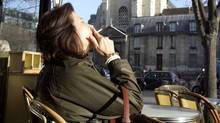 A woman smokes a cigarette on the pavement terrace of Les Deux Magots cafe-restaurant at Saint Germain des Pres square in Paris, Jan. 2, 2008 (Remy de la Mauviniere/The Associated Press)
