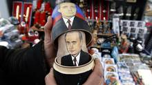 A seller demonstrates a traditional Matryoshka doll, or Russian nesting dolls, bearing the faces of presidential candidate and current Prime Minister Vladimir Putin and President Dmitry Medvedev in St. Petersburg March 3, 2012. Russians will go to the polls for their presidential election on Sunday. (ALEXANDER DEMIANCHUK)