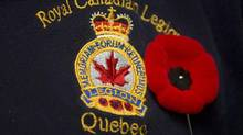 A poppy is pinned next to a Royal Canadian Legion crest in Montreal, November 2, 2012. (Graham Hughes/THE CANADIAN PRESS)