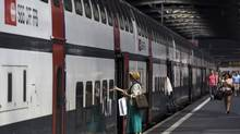 Passengers walk on a platform to enter a Swiss Federal Railways train at the main station in Zurich, on May 24, 2012. (Michael Buholzer/Reuters)