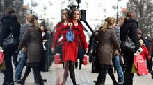 Shoppers are reflected in a shop window as they walk along Oxford Street, one of the main shopping streets in central London, in this file photo. (BEN STANSALL/AFP/Getty Images)