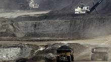 Mining trucks carry loads of oil-laden sand at the Albian Sands oil sands project in Fort McMurray, Alta. (JEFF McINTOSH/JEFF McINTOSH/ASSOCIATED PRESS)