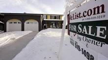 A 'for sale' sign is seen in front of a Calgary home in this file photo. (TODD KOROL For The Globe and Mail)