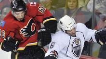 Calgary Flames T.J Brodie (L) hits Edmonton Oilers Colin Fraser against the boards during the second period of their pre-season NHL hockey game in Calgary, Alberta, October 3, 2010. REUTERS/Todd Korol (TODD KOROL)