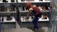 A clerk straightens out her display at a shoe store in Salem, New Hampshire. The U.S. Commerce Department's third and final estimate of second-quarter economic growth release Thursday was 1.3 per cent, compared with an earlier reading of 1.7 per cent. (Elise Amendola/Associated Press)