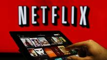 A man scrolls through a selection of viewing choices on the Netflix application in this arranged photograph in London, U.K., on Tuesday, Jan. 5, 2016. The company has 31 of its own original series it can show anywhere around the globe, but the content it licenses from other sources is often subjected to 'sliced and diced' territorial rights. (Chris Ratcliffe/Bloomberg)