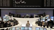 Traders are pictured at their desks in front of the DAX board at the Frankfurt stock exchange, Sept. 21, 2012. (Lizza May David/Reuters)
