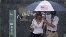 Spectators seek shelter from the heavy rains at Muirfield Village