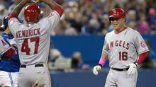 Los Angeles Angels' Hank Conger, right, is congratulated by teammate Howie Kendrick after hitting a three-run homer off Toronto Blue Jays pitcher Marcus Stroman during sixth-inning AL action in Toronto on Sunday, May 11, 2014. (Frank Gunn/THE CANADIAN PRESS)