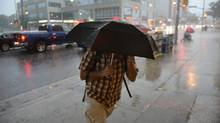 A pedestrian heads for the protection of a covered doorway of a building in Toronto on July 19, 2013, as heavy rain and thunderstorms hammered Southern Ontario. (FRED LUM/THE GLOBE AND MAIL)