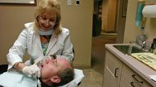 Dental hygienist Joan Shebaylo seen with her patient Derek Okarmus in for a teeth cleaning. (LOUIE PALU/THE GLOBE AND MAIL/The Globe and Mail)