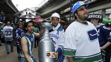 Vancouver Canucks fans carry a replica of the Stanley Cup before the Canucks play the Boston Bruins in Game 1 of the NHL Stanley Cup Final hockey playoff in Vancouver, British Columbia June 1, 2011. (MIKE BLAKE/REUTERS)