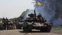 Ukrainian army tanks move past a checkpoint as they patrol the area near eastern Ukrainian town of Debaltseve Aug. 3. (VALENTYN OGIRENKO/REUTERS)