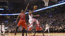 The Toronto Raptors' Kyle Lowry, centre, scores on the Chicago Bulls' Jimmy Butler during the first half of their game in Toronto on Monday. For the results and game story, visit globesports.com (Chris Young/THE CANADIAN PRESS)