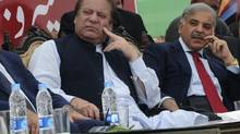 Former Pakistani premier Nawaz Sharif, left, and his brother and Punjab province Chief Minister Shahbaz Sharif attend the launch of the Metrobus system in Lahore on Feb. 10. (ARIF ALI/AFP)