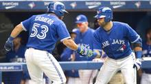 Toronto Blue Jays Melky Cabrera is congratulated by teammate Jose Bautista after he hit a solo home run against the Texas Rangers in the seventh inning of their AL baseball game in Toronto, Sunday, July 20, 2014. (Fred Thornhill/THE CANADIAN PRESS)
