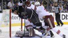 Los Angeles Kings' Jeff Carter (L) is checked by Phoenix Coyotes' Rostislav Klesla in front of Coyotes goalie Mike Smith during the first period of Game 4 of their NHL Western Conference final playoff hockey game in Los Angeles, California, May 20, 2012. (LUCY NICHOLSON/REUTERS)