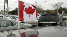 A Canadian flag flies from the window of a General Motors vehicle at a car dealership in Toronto (MIKE CASSESE/REUTERS)
