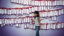 A girl stands in front of message cards for passengers onboard the missing Malaysia Airlines Flight 370 at a shopping mall in Kuala Lumpur, Malaysia, Friday, April 11, 2014. (Vincent Thian/AP)
