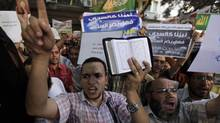 People shout and hold slogans in front of the U.S. embassy during a protest in Cairo September 11, 2012. (MOHAMED ABD EL GHANY/REUTERS)