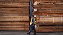 A worker walks past stacks of lumber at the Partap Forest Products mill in Maple Ridge, B.C. (DARRYL DYCK/THE CANADIAN PRESS)