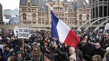 A man uses a hockey stick as a flag pole as hundreds of people hold a moment of silence for the victims of the recent French terrorist attacks during a demonstration of support for free speech in Toronto on Sunday, January 11, 2015. (Darren Calabrese/THE CANADIAN PRESS)