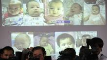 Surrogate babies that Thai police suspect were fathered by a Japanese businessman who has fled from Thailand are shown on a screen during a news conference at the headquarters of the Royal Thai Police in Bangkok on Aug. 12, 2014. Thai police said last Friday they had found four more babies they suspect were fathered by the Japanese businessman, bringing the total to 13 discovered in Bangkok that week. (ATHIT PERAWONGMETHA/REUTERS)