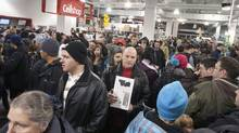 Hundreds of people, some of them who lined up since 6:30 am, grabs items from piles while shopping at a Future Shop for Boxing Day sales at Laurier shopping mall in Quebec City on Sunday, December 26, 2010. THE CANADIAN PRESS/Jacques Boissinot