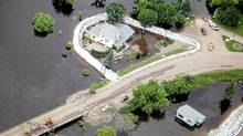 Homes are surrounded by water in Souris, Man. on Monday July 4, 2011. (Tim Smith/The Canadian Press)