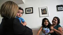 Ontario NDP Leader Andrea Horvath, left, pays a visit to Cristina Carbajal and her two children on Sept. 12, 2011. (Anna Mehler Paperny/The Globe and Mail)