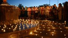 Sikh women and men hold candles during a prayer vigil at the Sikh Religious Society temple in Palatine, Il. on Monday, Aug. 6, 2012. The vigil was held in memoriam of those killed and wounded in a weekend Sikh temple shooting near Milwaukee. (AP photo / Daily Herald, Mark Welsh) (Mark Welsh/AP)
