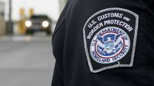 U.S. Customs and Border Protection (CMP) officer, stands near security booth as vehicles approach in Detroit, Mich., in this file photo. (DAVE CHIDLEY/The Canadian Press)